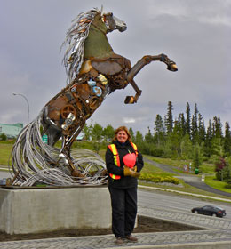 a happy artist in front of the mounted horse sculpture.